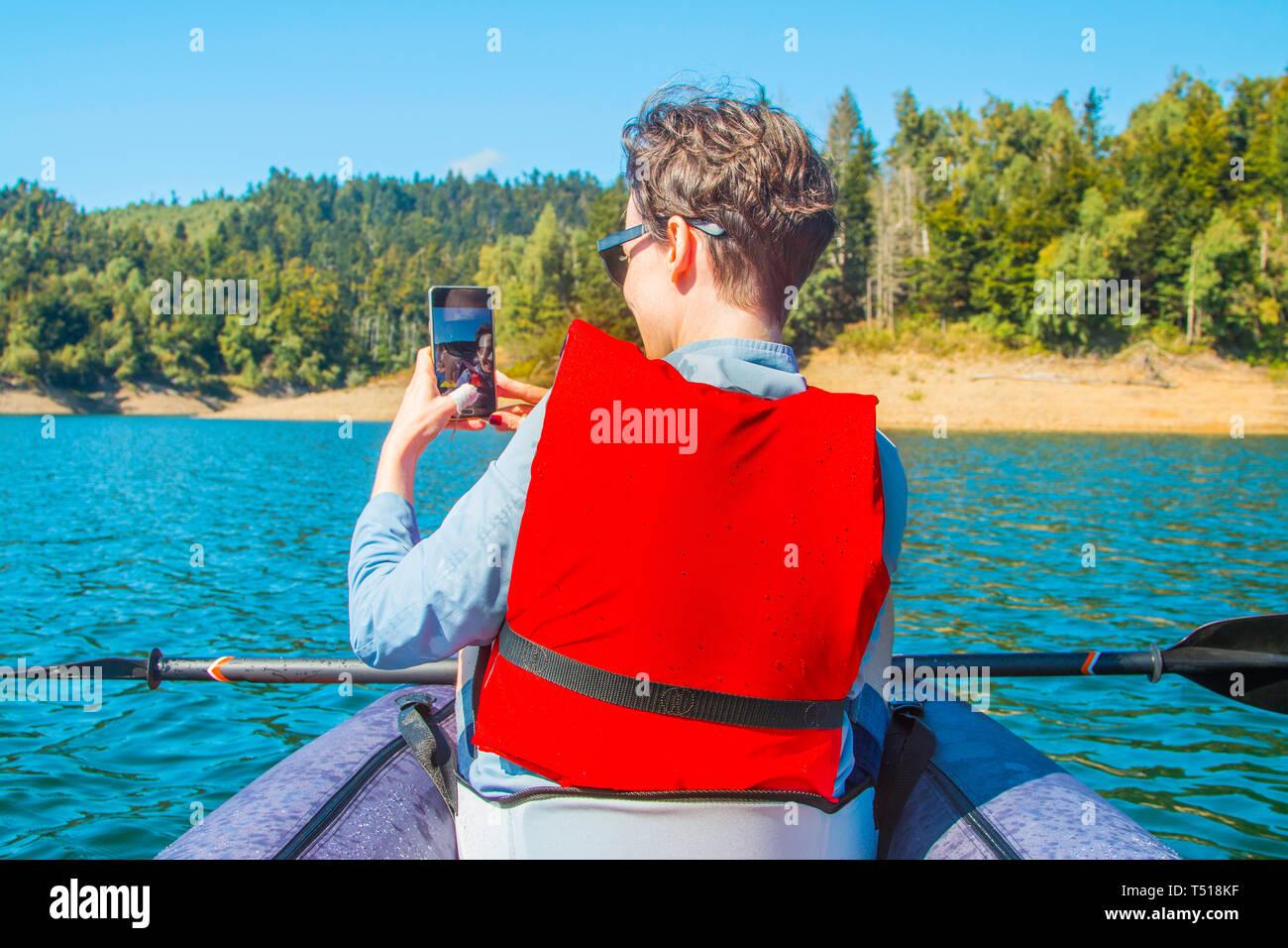 Selfie en el lago. Mujer joven tomando autorretrato con smart phone en kayak en el lago Lokvarsko en Gorski Kotar, Croacia. La mujer disfruta de aventuras Foto de stock