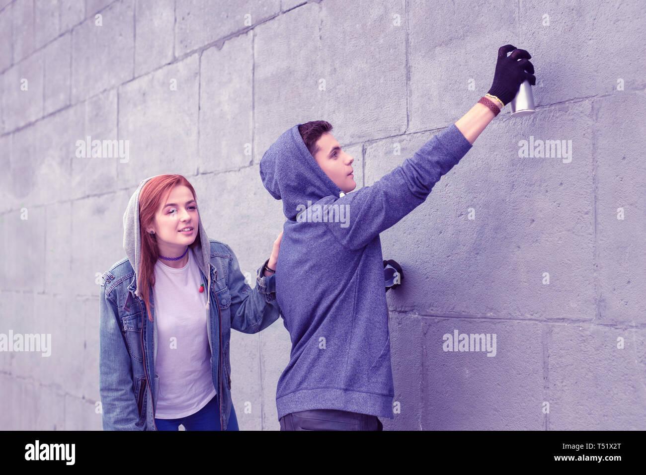 Peligroso joven ciudad para colorear las paredes con pinturas de spray Foto de stock