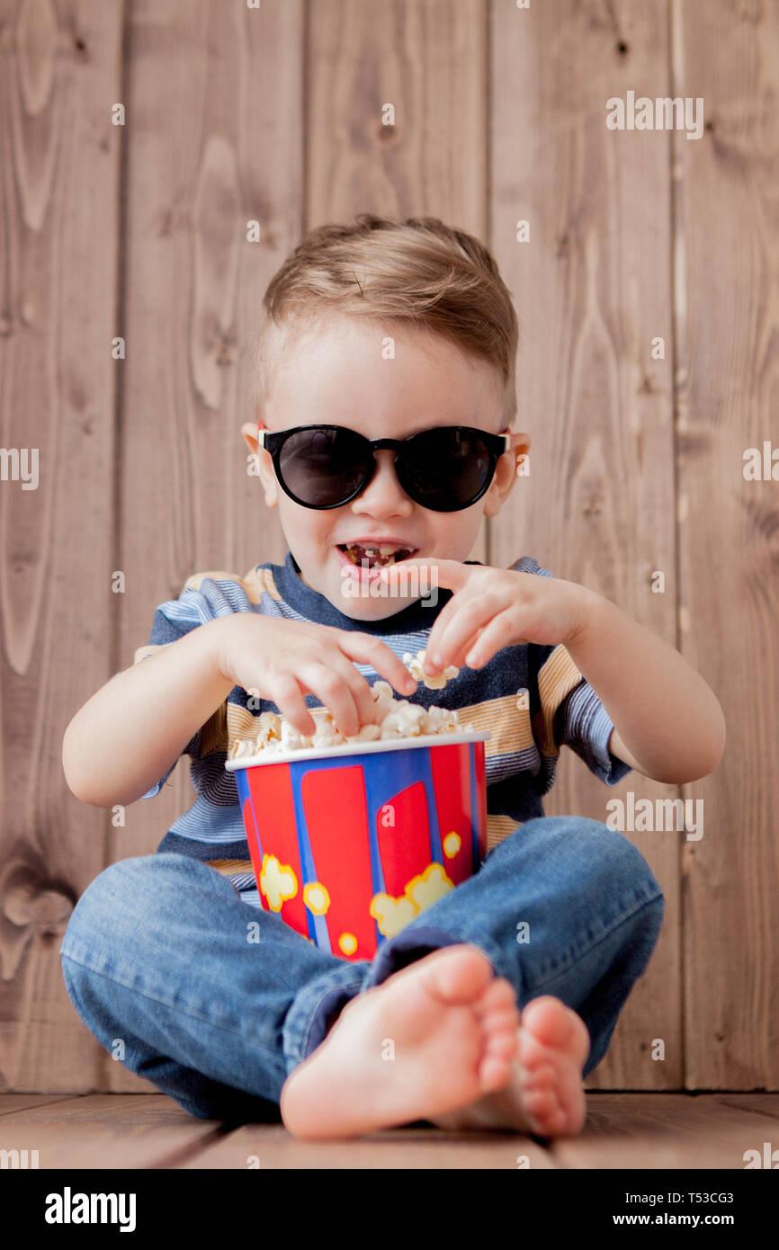 8f66e295ae Poco chico lindo bebé niño 2-3 años , 3D IMAX cinema gafas sosteniendo la  cuchara para palomitas, comer comida rápida sobre fondo de madera.