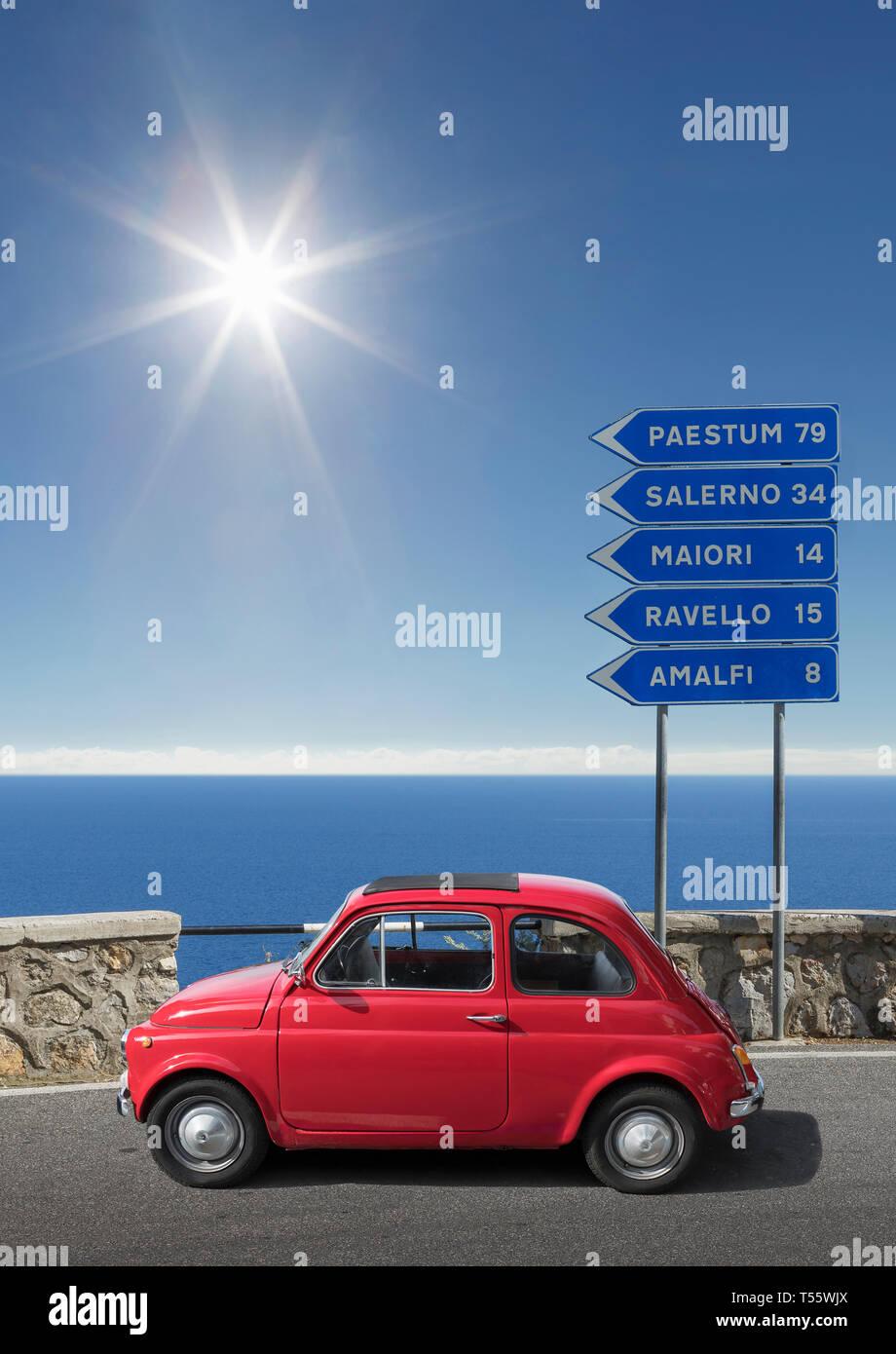 Coche rojo por señales de carretera en Costa de Amalfi, Italia Foto de stock