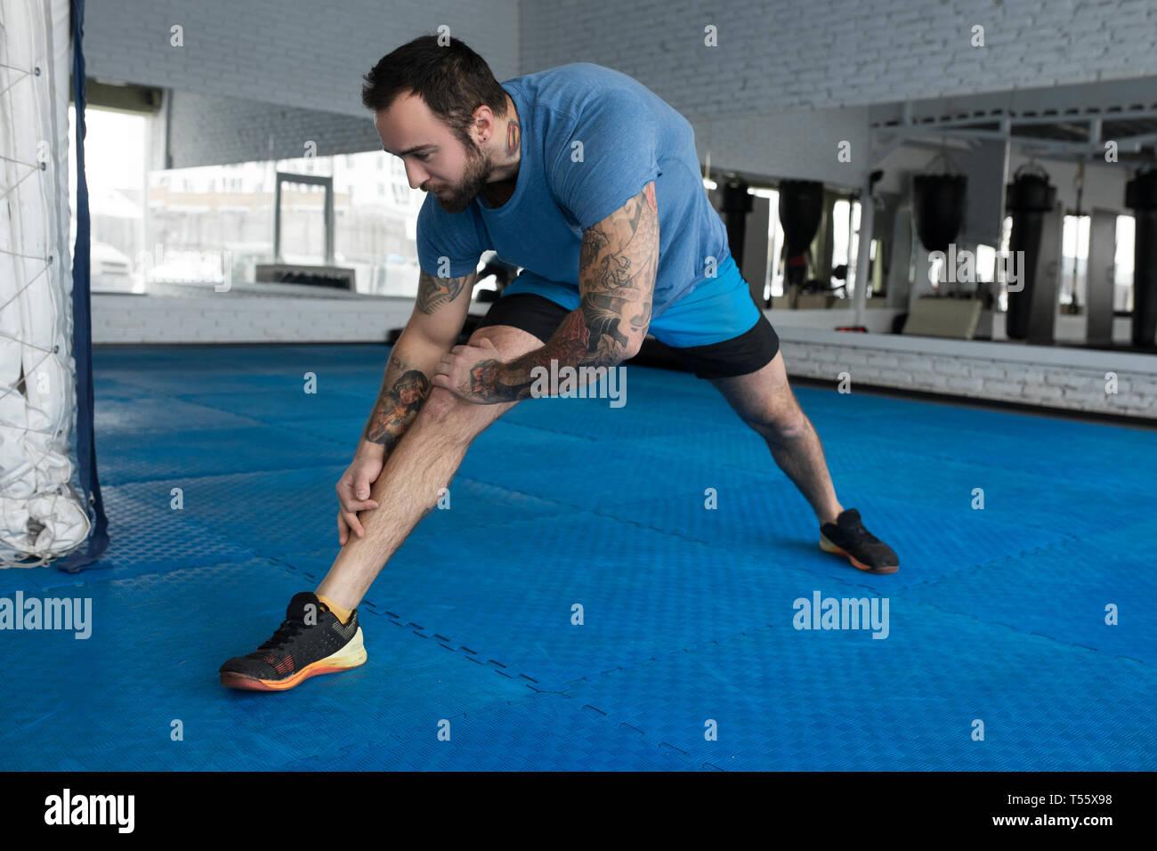 Mitad hombre adulto estiramiento en el gimnasio Foto de stock