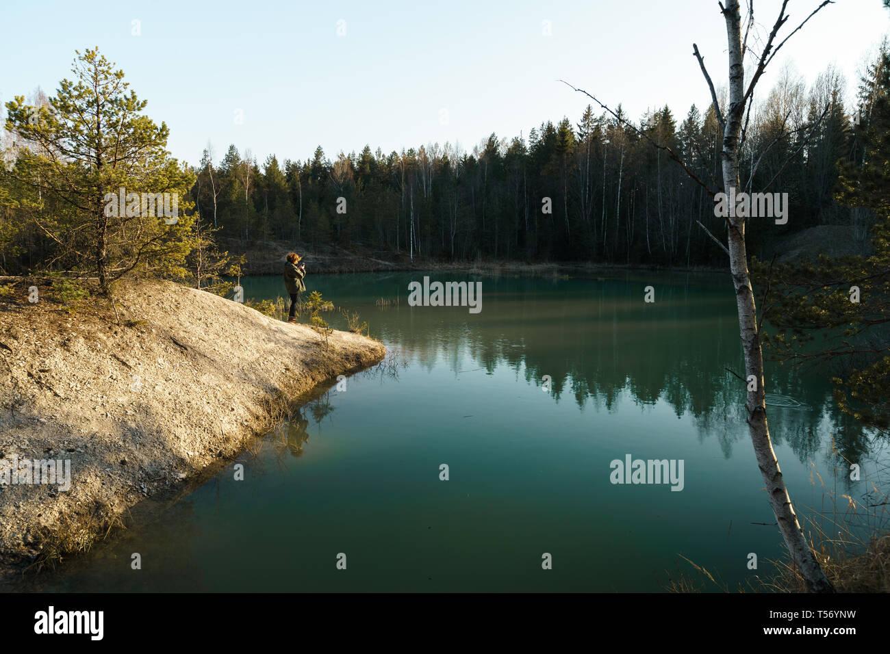 Joven toma fotos de viajes -hermoso lago Turquesa en Letonia - estilo Meditirenian colores en Estados bálticos - Lackroga ezers Foto de stock