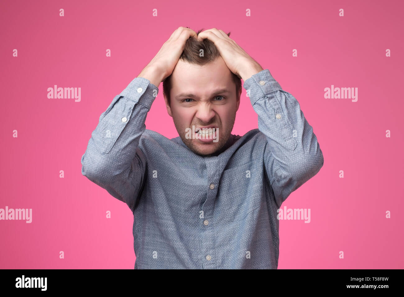 Enojado gritando joven poniendo las manos en la cabeza en la pared rosa en studio. Imagen De Stock