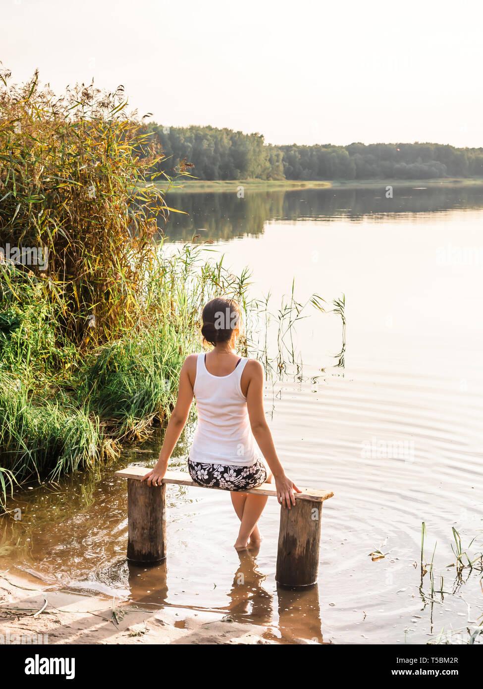 0059097f5 Pensativo niña sentada en un banco del río y disfruta de un hermoso  atardecer. Chica