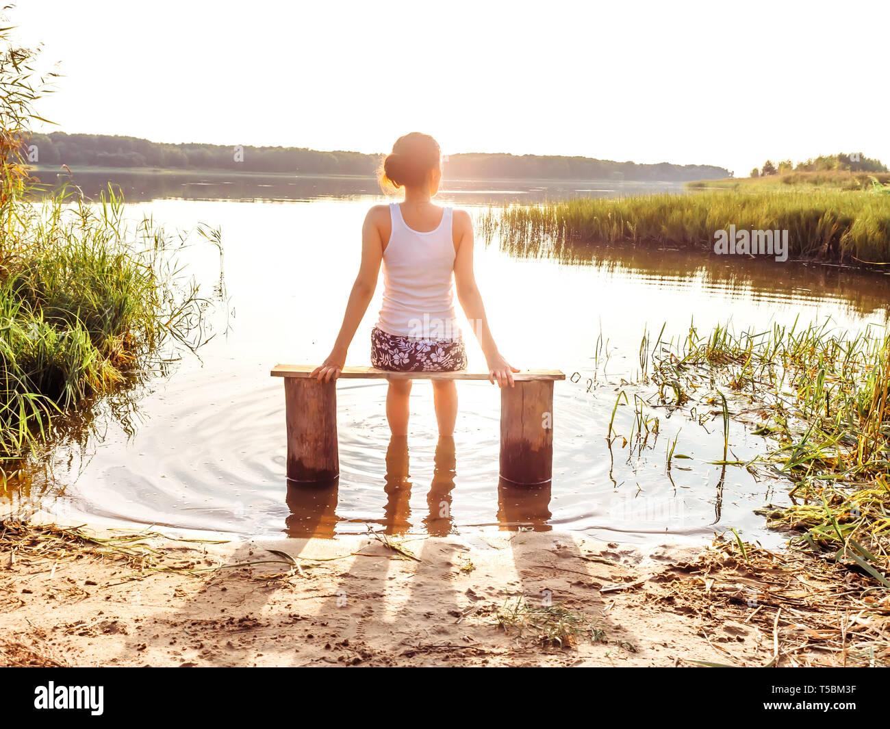 b18f8b455 La niña disfruta de un hermoso atardecer sentado en un banco en el río.  Chica