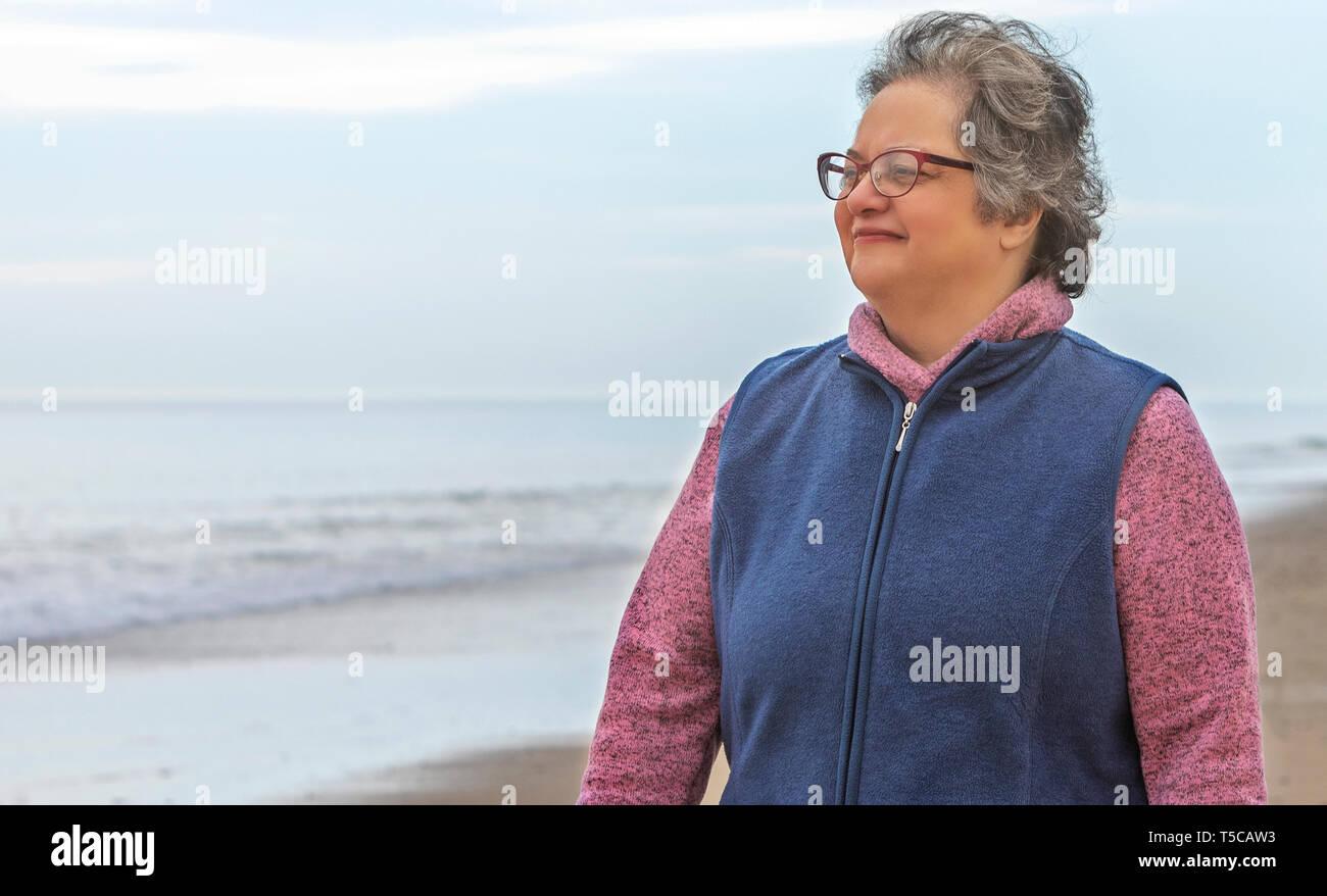 Una mujer mayor disfrutando de caminar en la arena de la playa por la orilla del océano. Imagen De Stock