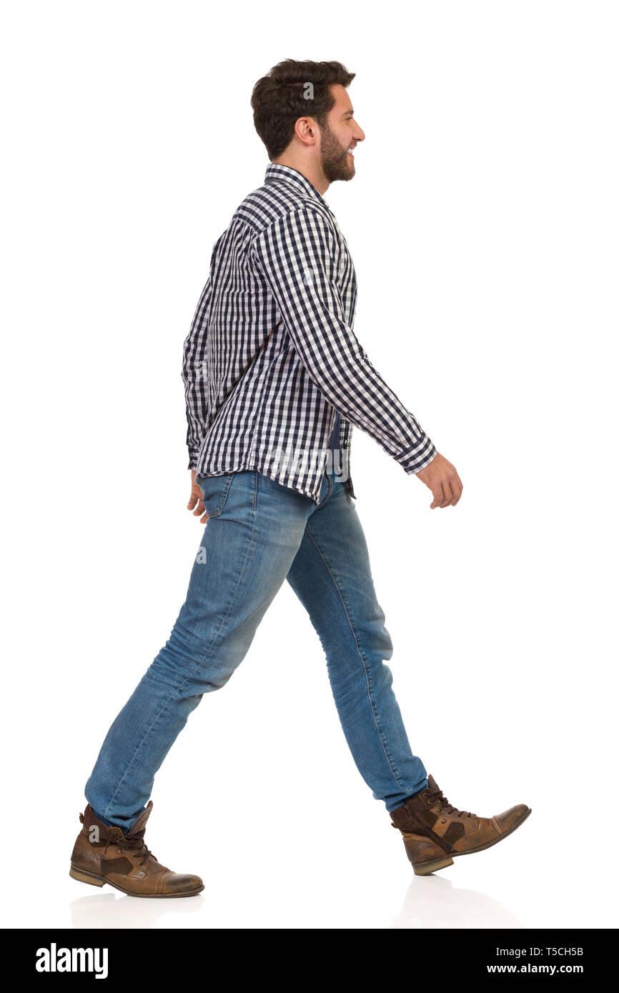 El hombre está caminando en botas, pantalones vaqueros y