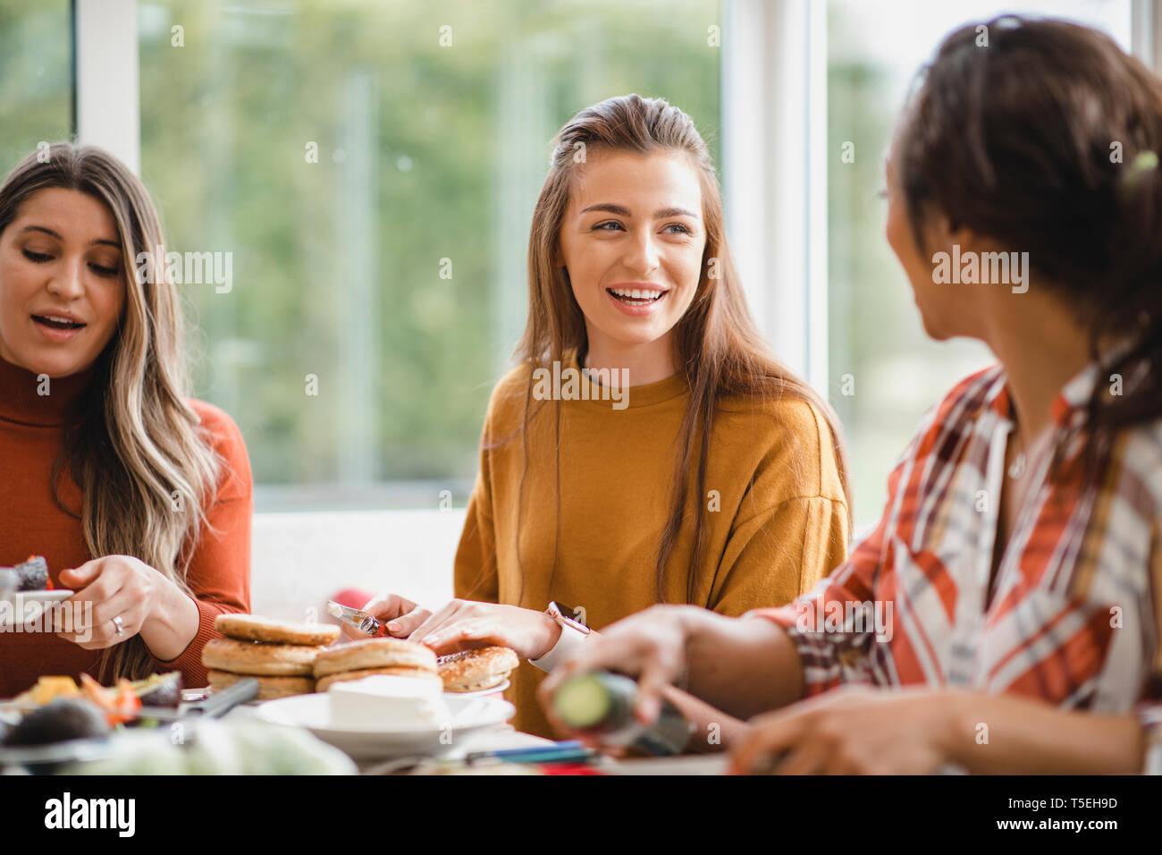 Las mujeres adultas jóvenes hablando con su amigo, mientras que con un almuerzo saludable. Están sentados dentro de un conservatorio, divirtiéndose. Foto de stock