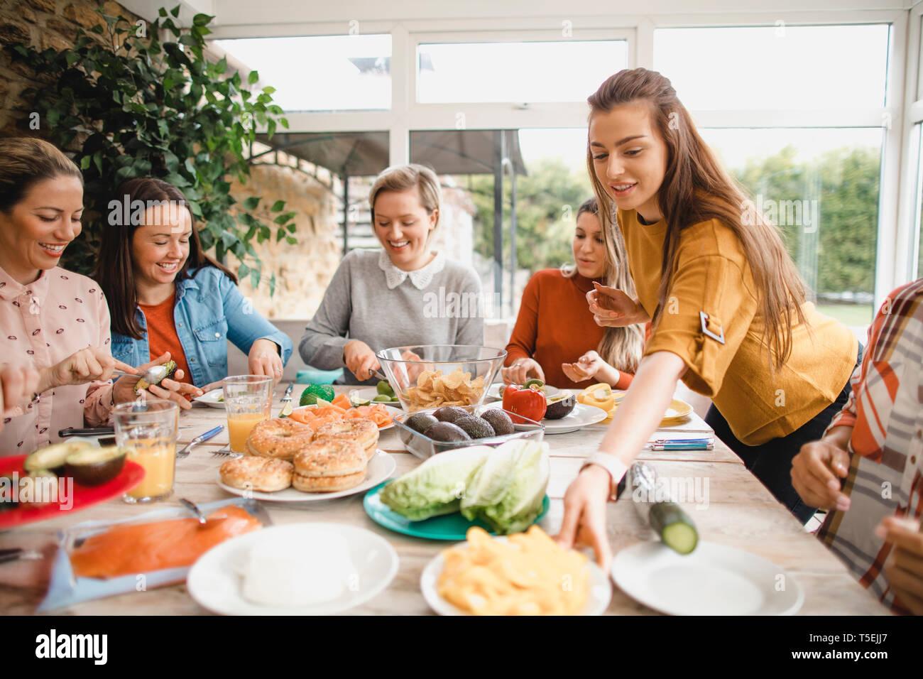 Un pequeño grupo de amigas preparan un almuerzo saludable dentro de un invernadero en una escapada de fin de semana. Foto de stock