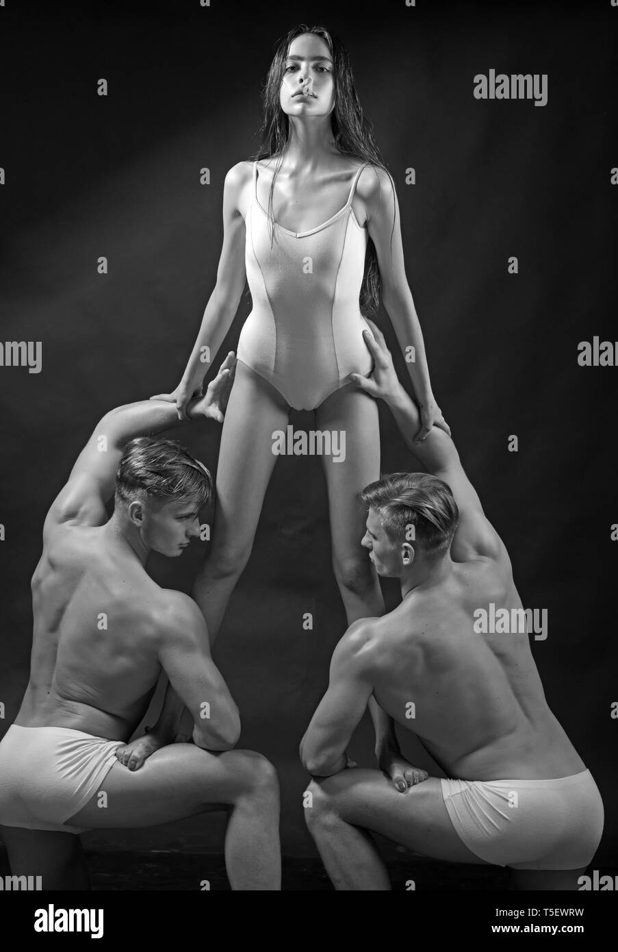 Flexibilidad en la acrobacia. flexibilidad muscular de hombres y mujer bonita en blanco sportswear. Imagen De Stock