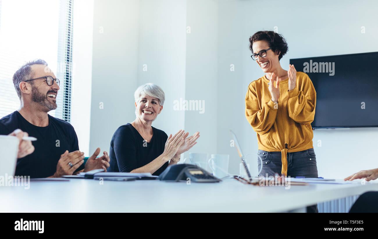 Los empresarios de las palmas después de la exitosa sesión de lluvia de ideas en la sala de juntas. Grupo de hombres y mujeres aplaudiendo tras la reunión productiva. Foto de stock