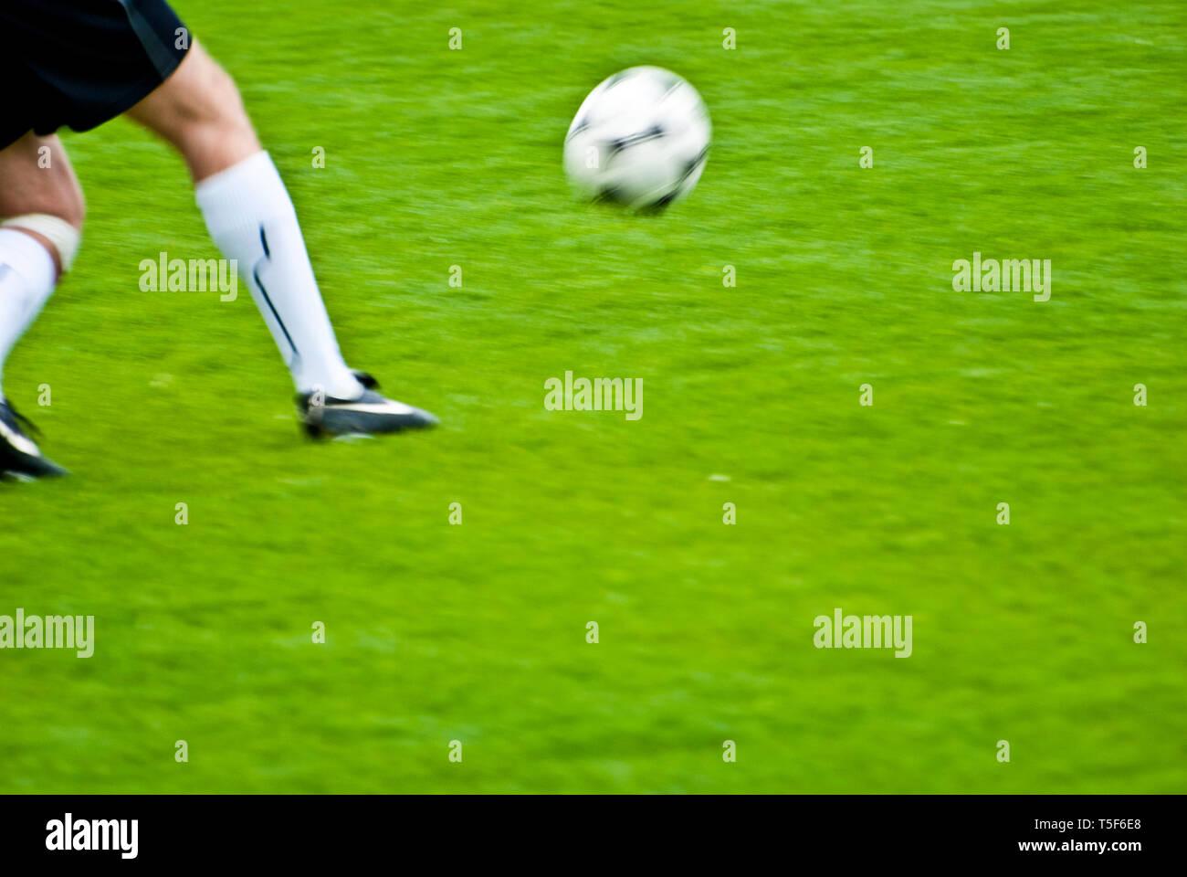 Las piernas y la bola de un jugador de fútbol durante un partido Foto de stock