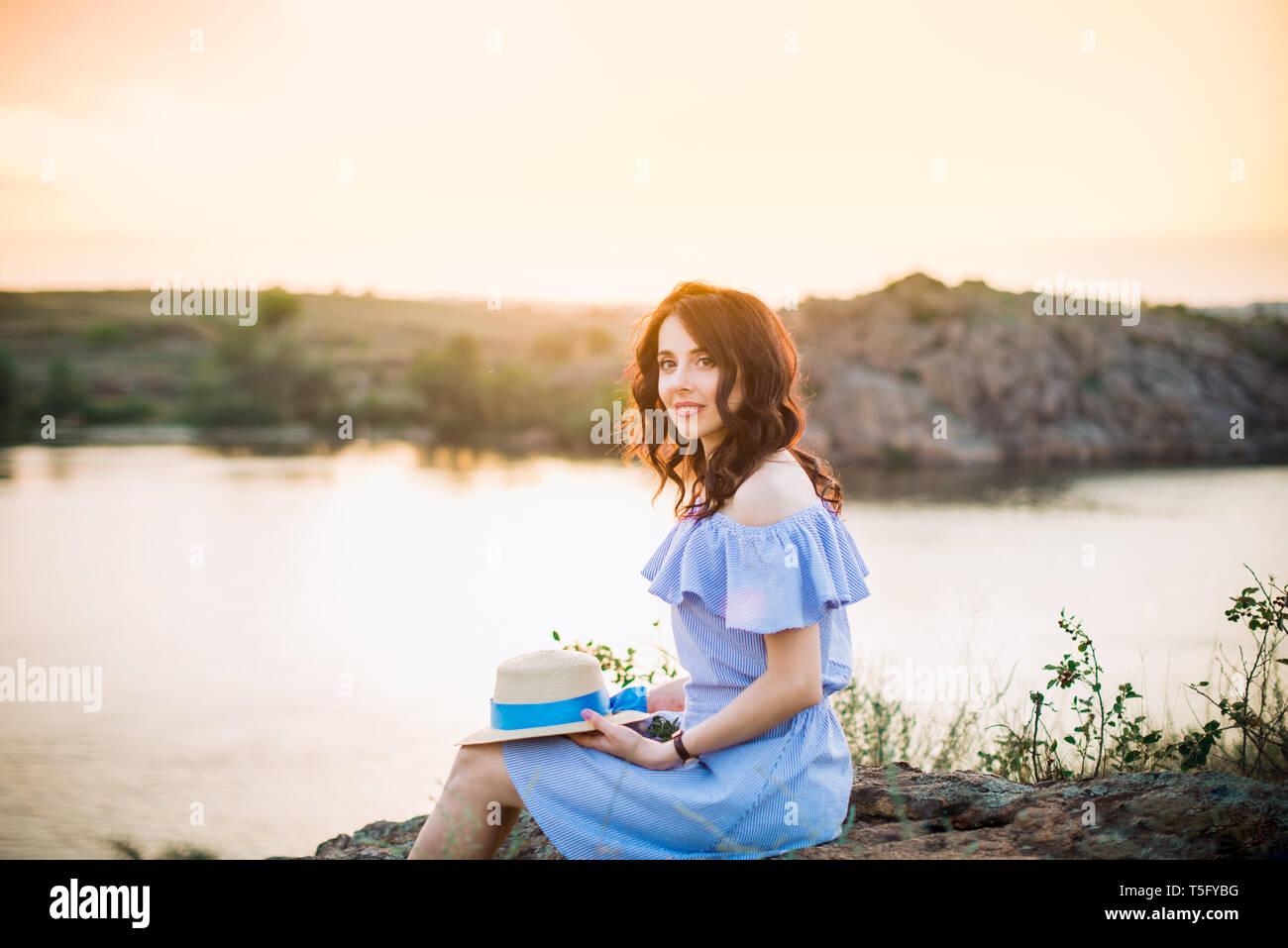 Retrato de joven mujer en azul vestido romántico con sombrero sentado cerca de río y disfrutar de la puesta de sol por la tarde. Tranquilidad y armonía. Vacaciones de Verano,divertido, positiv Imagen De Stock