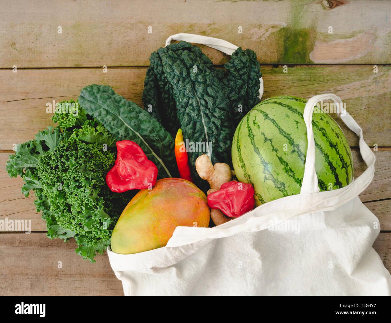 7667cd900 Bolsa de tela ecológica con verduras sobre fondo de madera de estilo  rústico. Vista desde