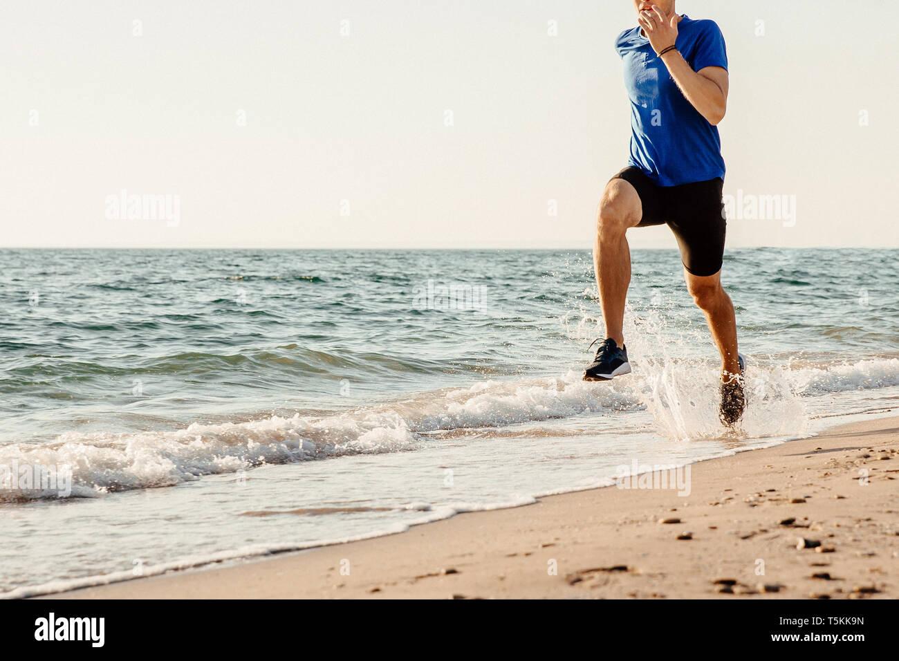 Deslizadera macho ejecuta en el mar de la playa de arena de spray de agua Foto de stock