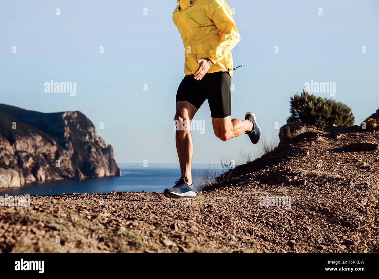 Deslizadera macho ejecuta sendero de montaña en la chaqueta amarilla Foto de stock