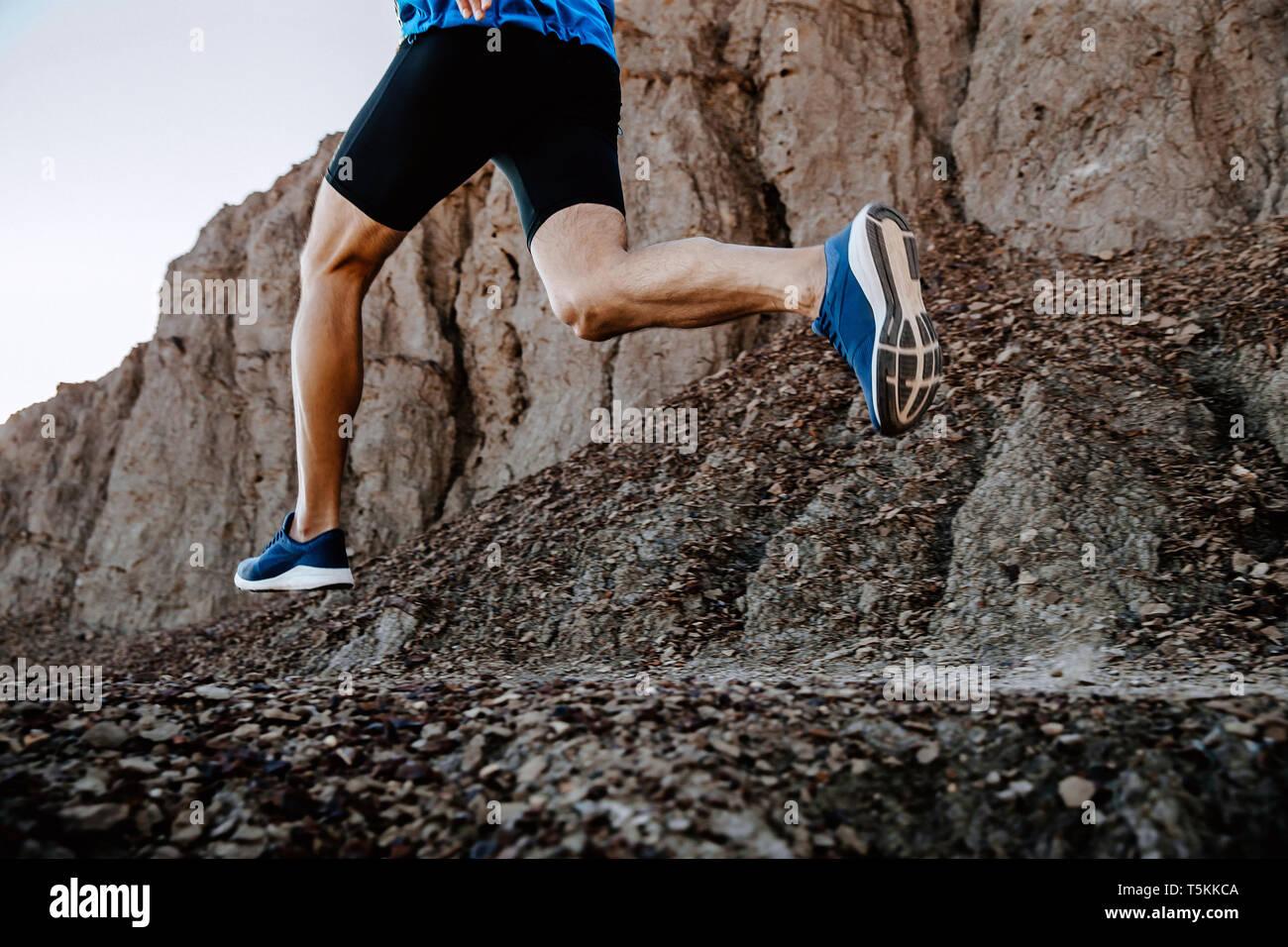 Piernas hombre runner corriendo en piedras de montaña trail Foto de stock