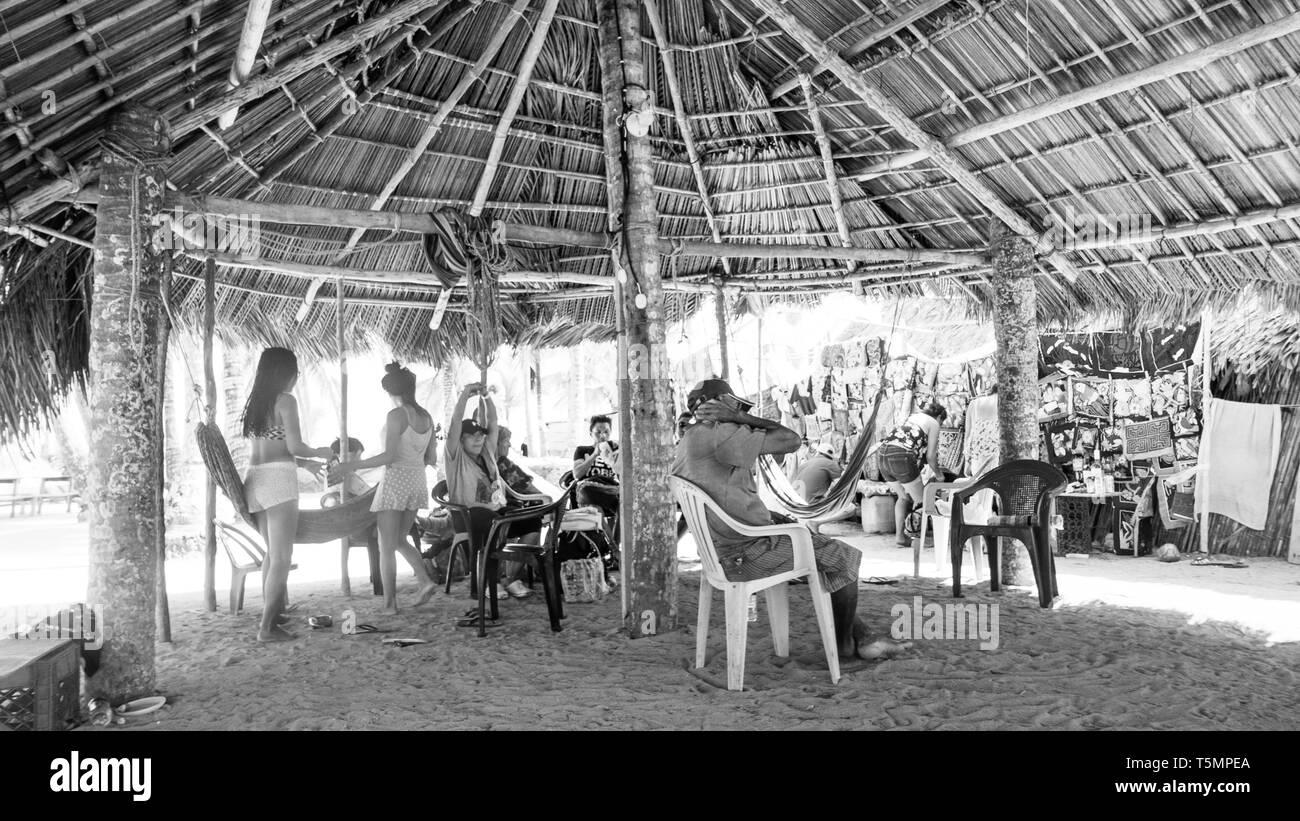Guna (kuna) miembros tribales comunal grande relajarse bajo una choza hecha con hojas de palmera, viendo como los turistas visitan su isla y comprar Molas Foto de stock
