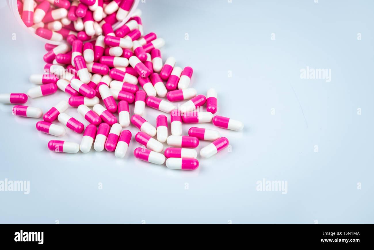 Cápsulas píldora rosa y blanco derramado de botella de plástico blanco. Concepto de salud global. Antibióticos la resistencia a los medicamentos. Ca antimicrobiana Foto de stock