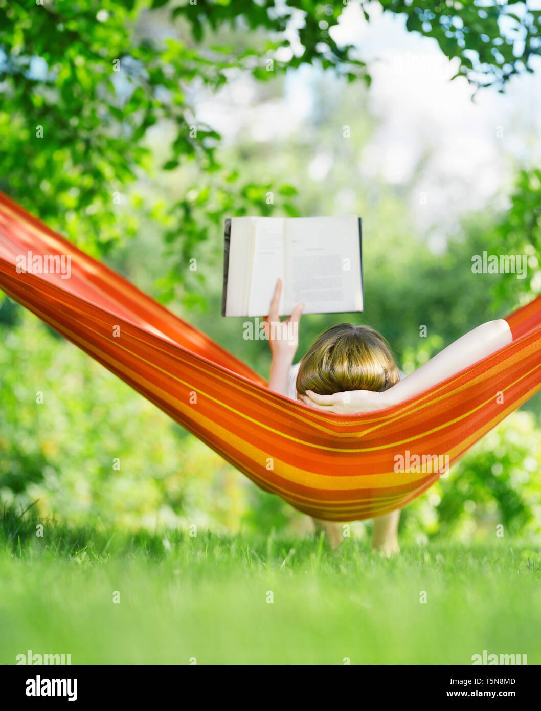 Mujer leyendo el libro en la hamaca Imagen De Stock