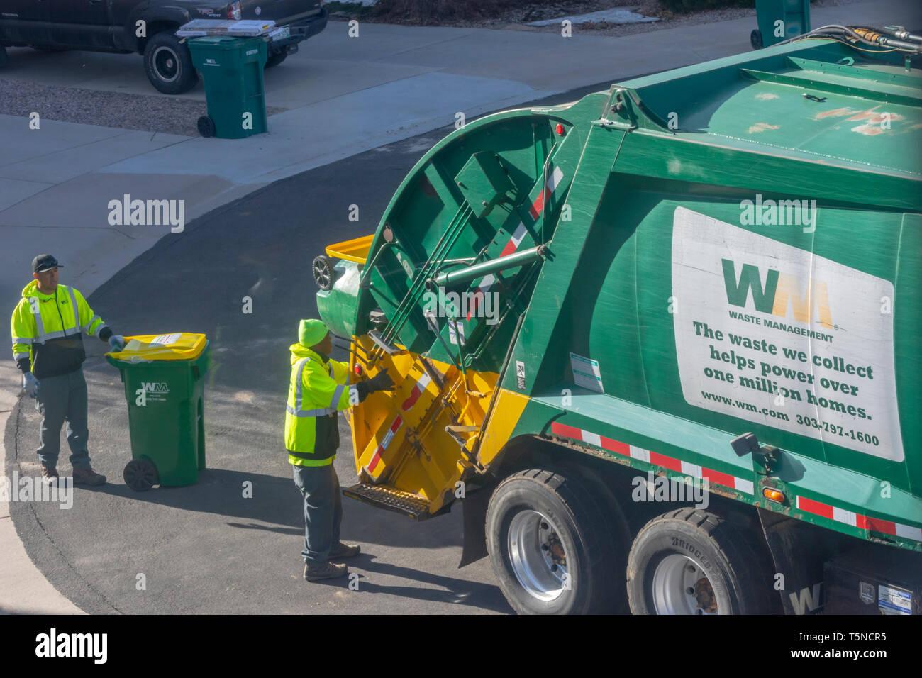 Dos trabajadores de gestión de residuos de plástico amarillo y verde vacío recipientes de basura en una zona residencial de Castle Rock, Colorado, EEUU. Foto tomada en abril. Imagen De Stock