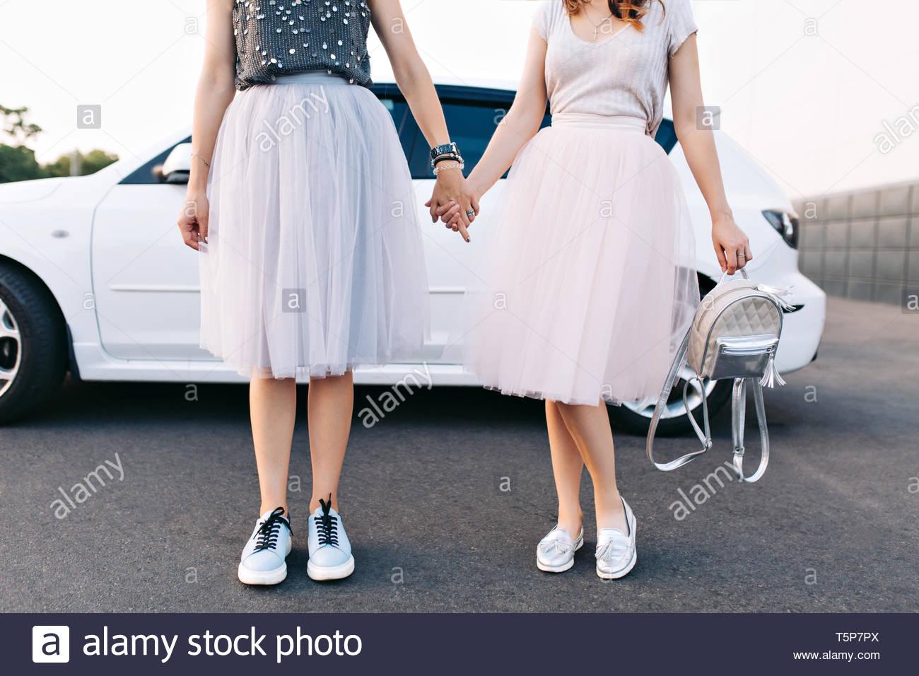 ac441a80a Cuerpos de modelos de moda en faldas de tul amd sneakers en coche blanco de  fondo. Ellos tomados de las manos · Look Studio / Alamy Foto de stock