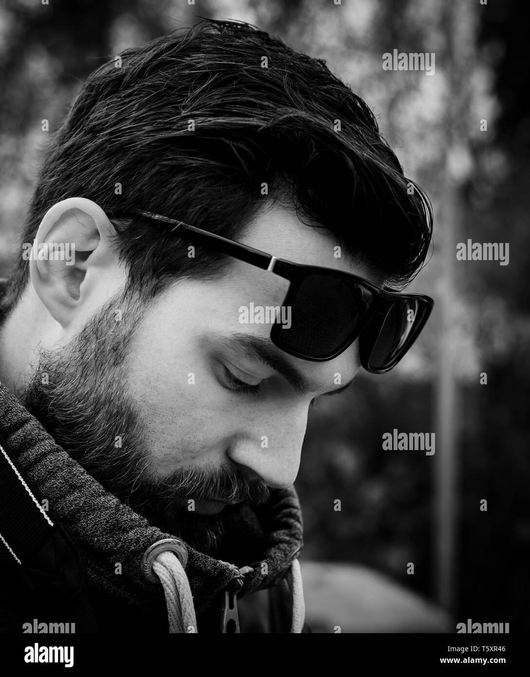 Atractiva joven hombre barbado con cabello oscuro y un jersey en el parque con gafas de sol Foto de stock
