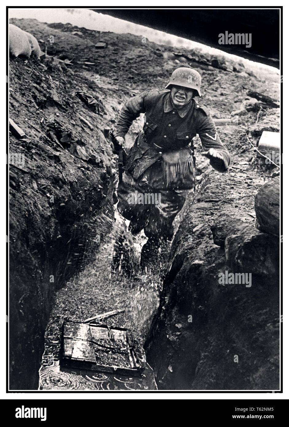 WW2 alemán trincheras reportaje notable imagen de la Alemania Nazi Wehrmacht Ejército messenger corriendo en la lluvia empapó zanja húmeda. El Frente Oriental. El frente oriental de la Segunda Guerra Mundial fue un conflicto entre la Alemania nazi y la Unión Soviética de 1941 a 1945. Imagen De Stock