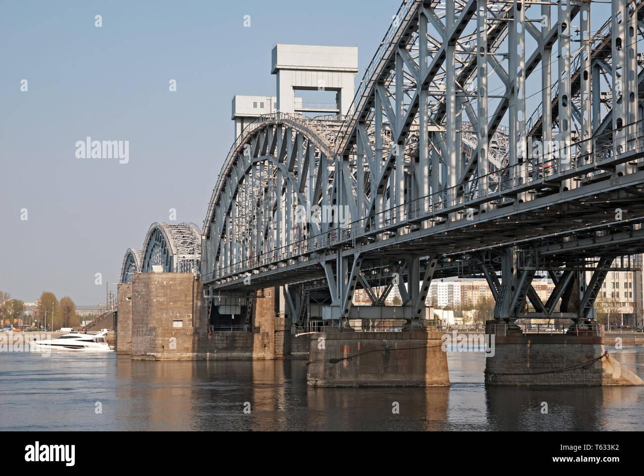 San Petersburgo, Rusia - Abril 26, 2019: un pequeño barco blanco sobre el río Neva, cerca de la Finlandia de un puente de ferrocarril en San Petersburgo Foto de stock