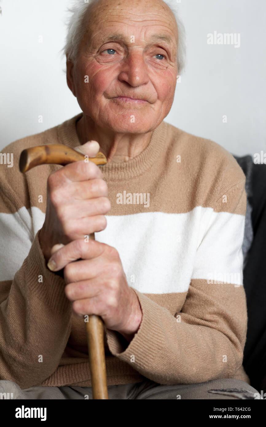 Retrato de un sonriente viejo hombre que puso sus manos sobre el mango de un bastón de madera, la salud en el hogar. Foto de stock