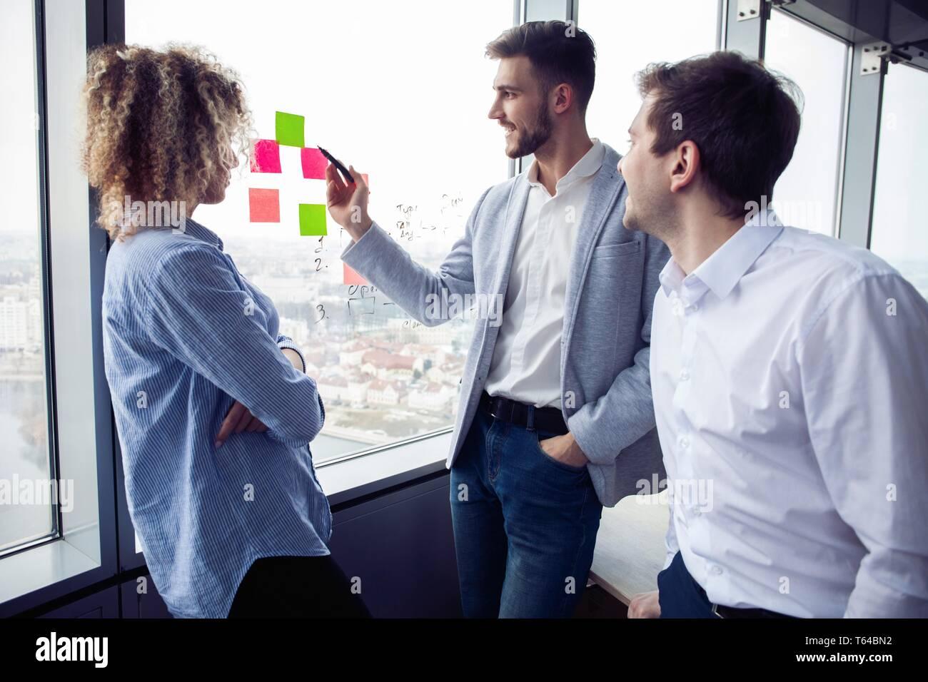 Grupo de jóvenes emprendedores están buscando una solución de negocios durante el proceso de trabajo en la oficina.La gente de negocios concepto de reunión Foto de stock