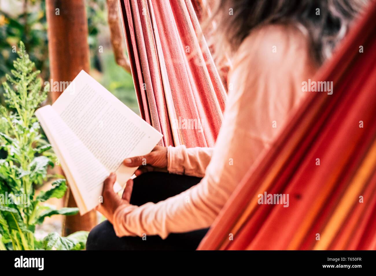 Leer un libro de papel antiguo estilo concepto para relajarse y estudiar - de edades caucsian mujer con cabello blanco sentado en una hamaca, disfrutar de las actividades de ocio al aire libre Foto de stock