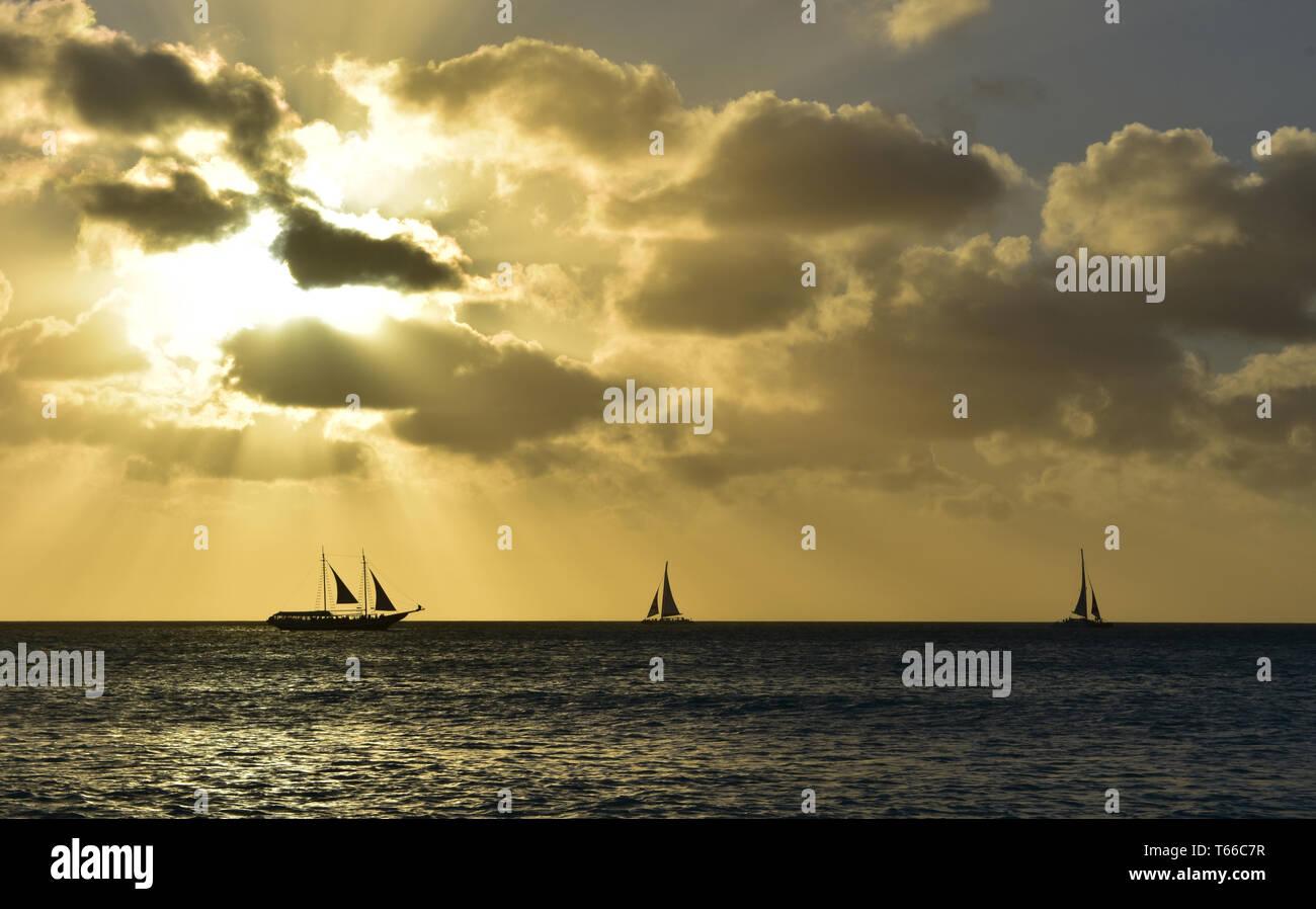Tres siluetas de veleros al atardecer en Aruba. Foto de stock