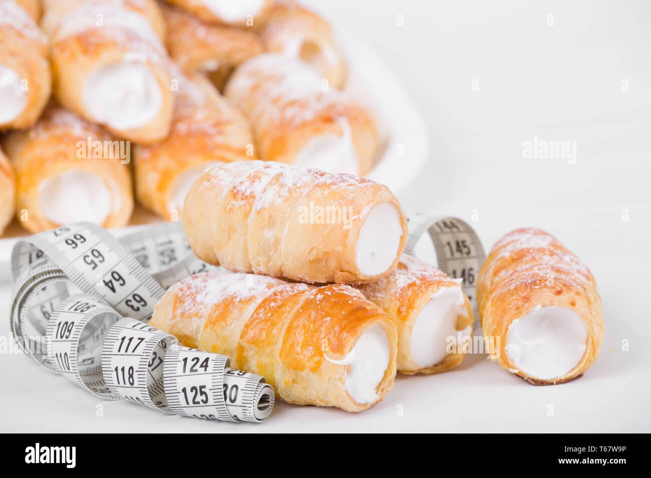Concepto de adelgazamiento, pasteles con cinta métrica Foto de stock