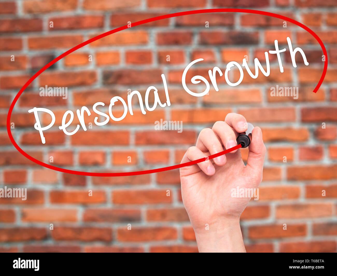 Hombre el crecimiento personal de escritura a mano con marcador negro en la pantalla visual Imagen De Stock