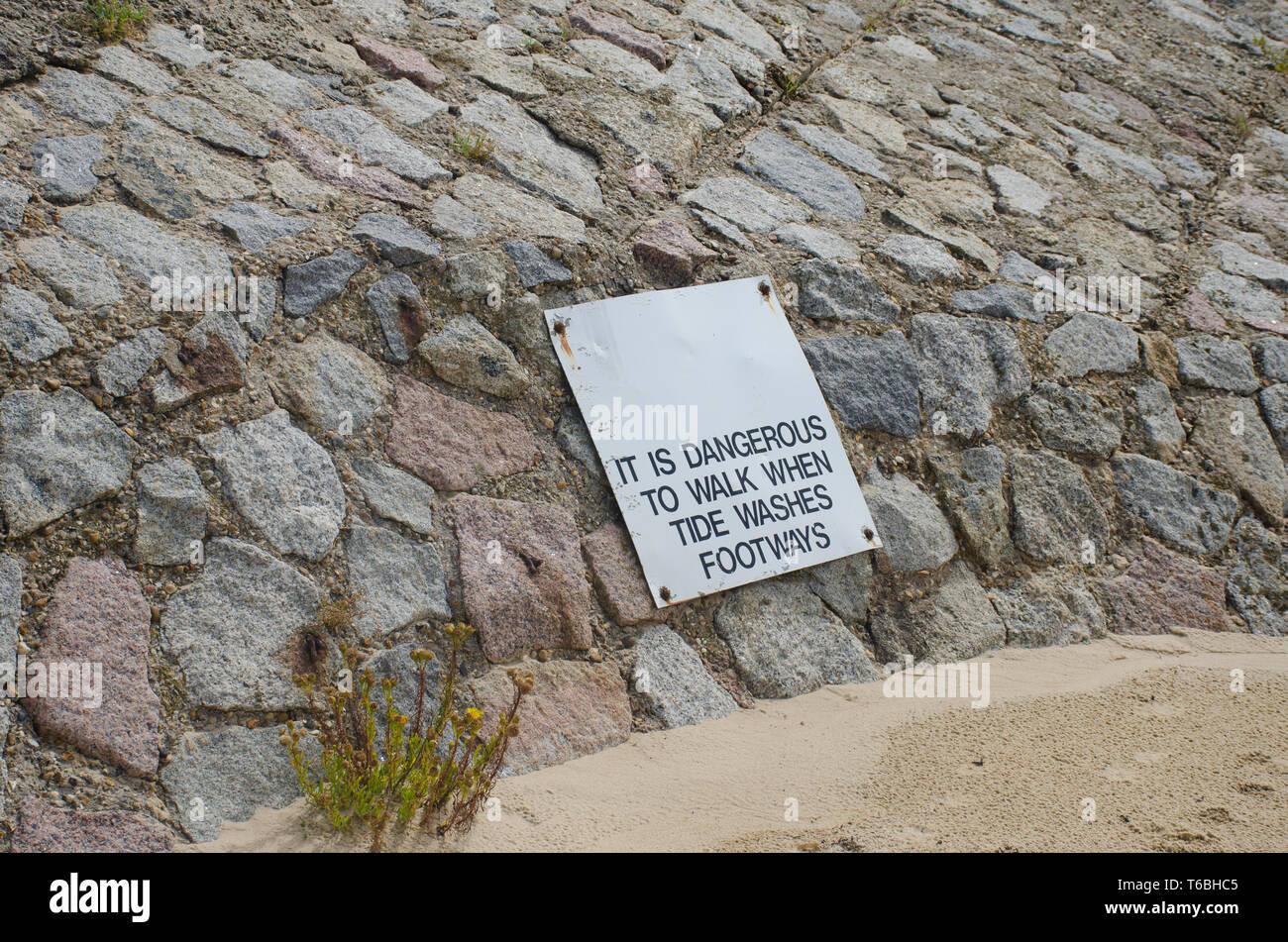Señal de advertencia en la ruta afectada por la erosión costera Imagen De Stock