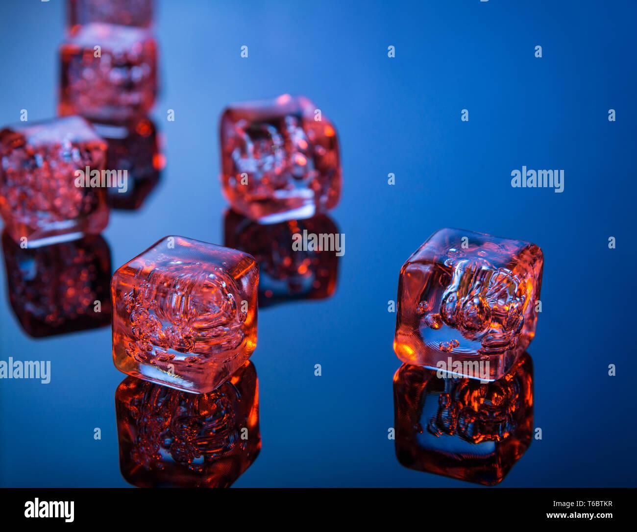Glowing cubitos de hielo en la superficie reflectante azul Foto de stock
