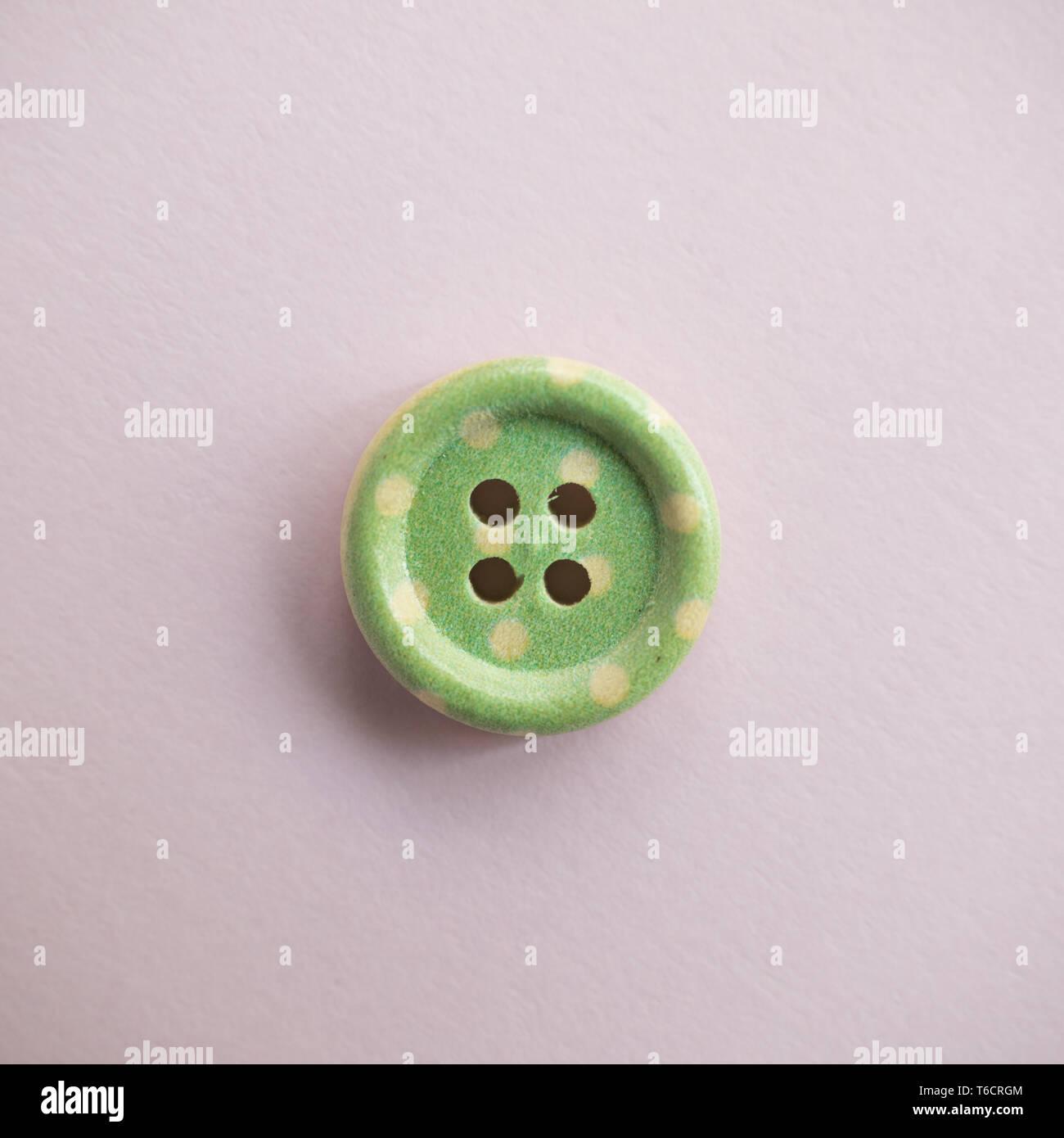 Botón de madera aislados con coloridos puntos de color rosa claro, costura de fondo Foto de stock