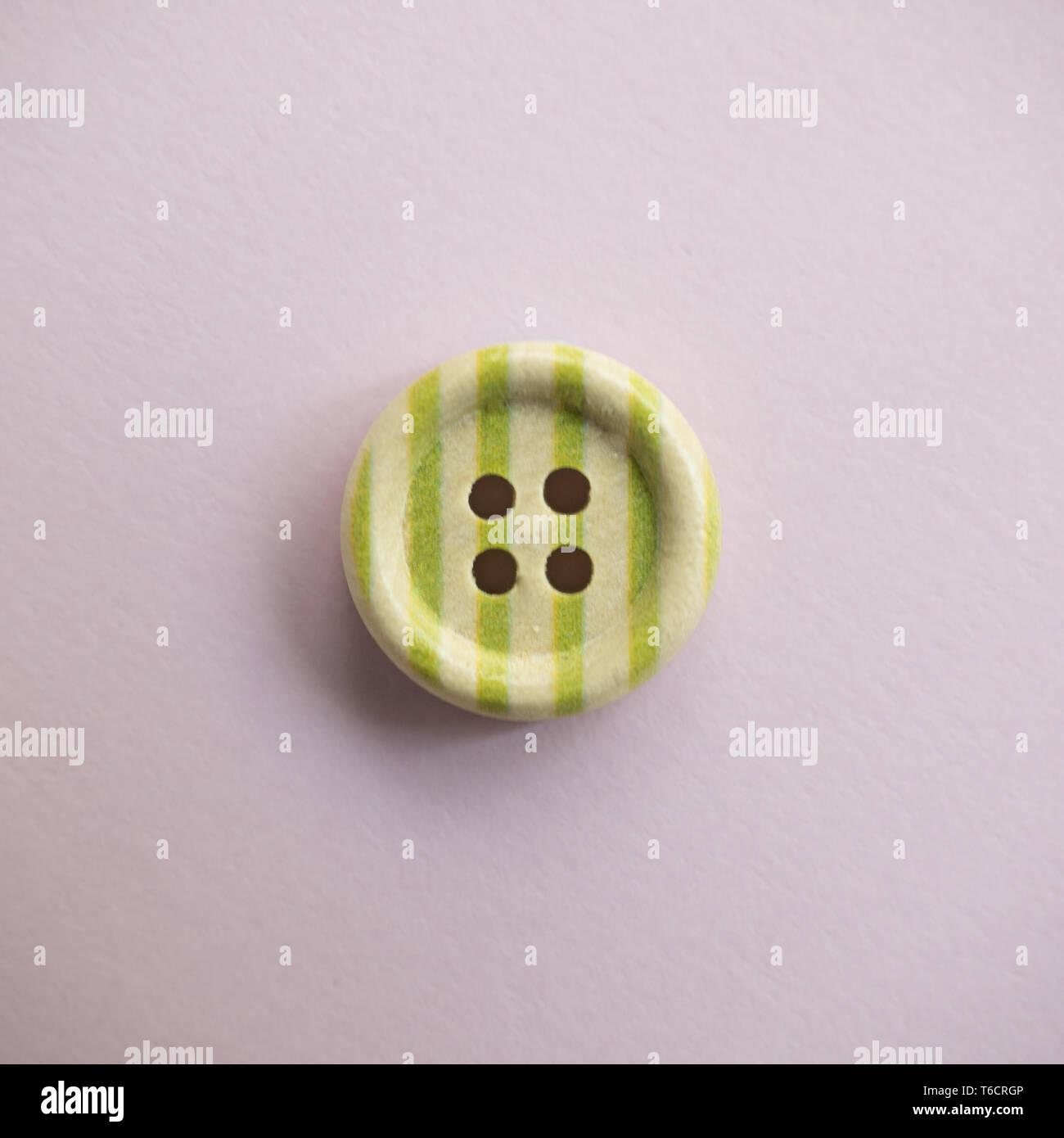 Botón de madera aislados con rayas coloridas de color sobre un fondo de color rosa claro, costura Foto de stock