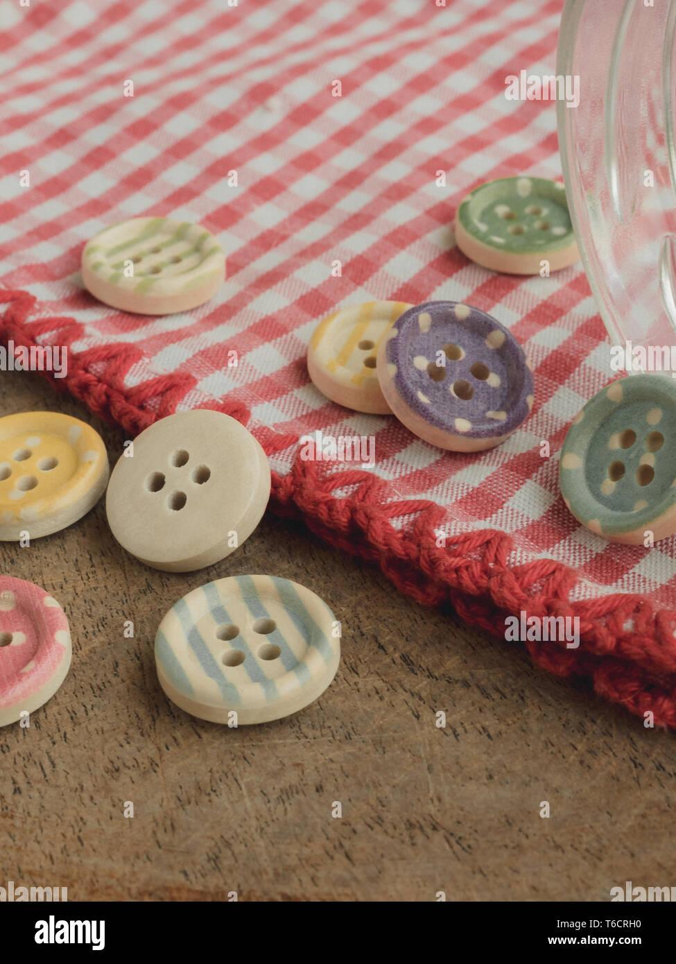 Botones de madera con tiras de colores de colores sobre un mantel de cuadros rojos y blancos, costura Imagen De Stock