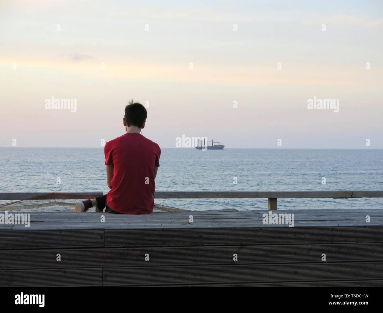 Joven sentada sola en el paseo mirando barco anclado frente a la costa, escuchando música ( concepto de soledad, relajación). Foto de stock