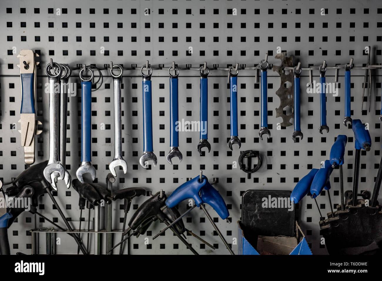 El taller del reparador, cerca bajo clave de imagen. Lugar de trabajo bien organizado de un mecánico, filas de llaves de tuercas y otras herramientas Foto de stock