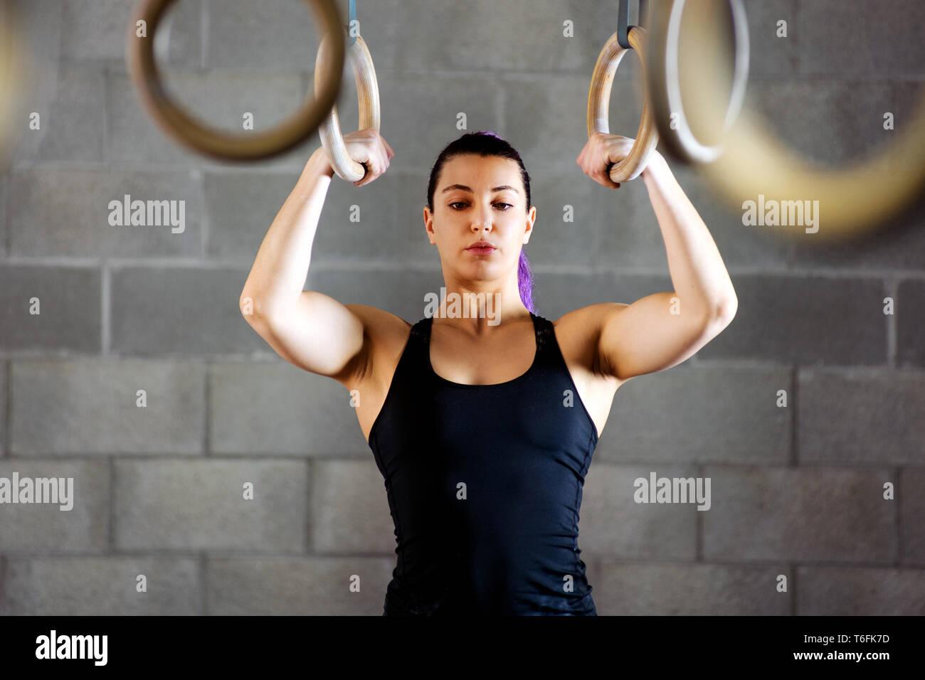 Joven atleta femenina concentrando antes de trabajar en la misma psyching anillos hasta comenzar su rutina de ejercicios en un gimnasio Imagen De Stock