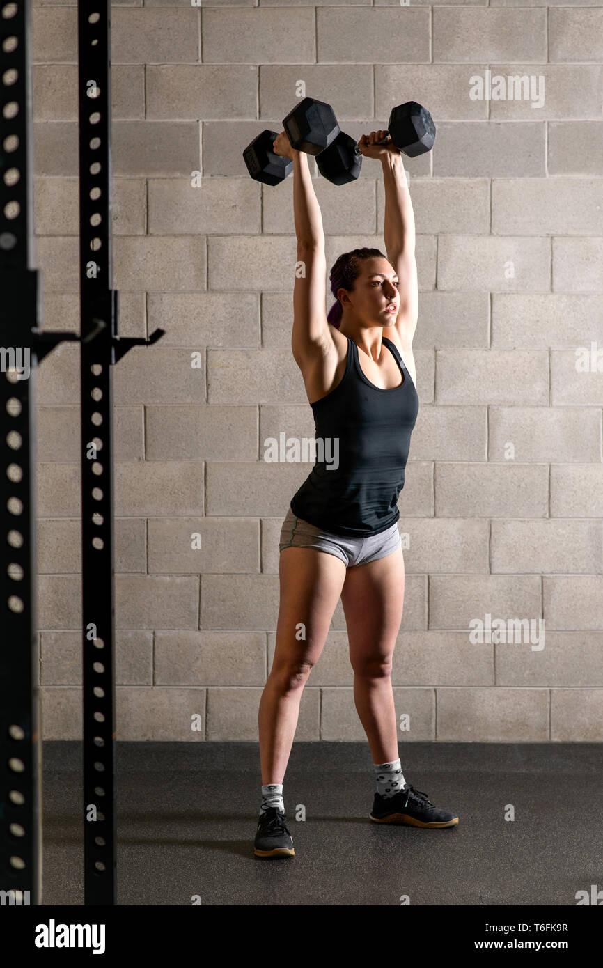 Colocar fuerte joven haciendo ejercicios de pesas levantando un par de pesas por encima de su cabeza dentro de un gimnasio Imagen De Stock