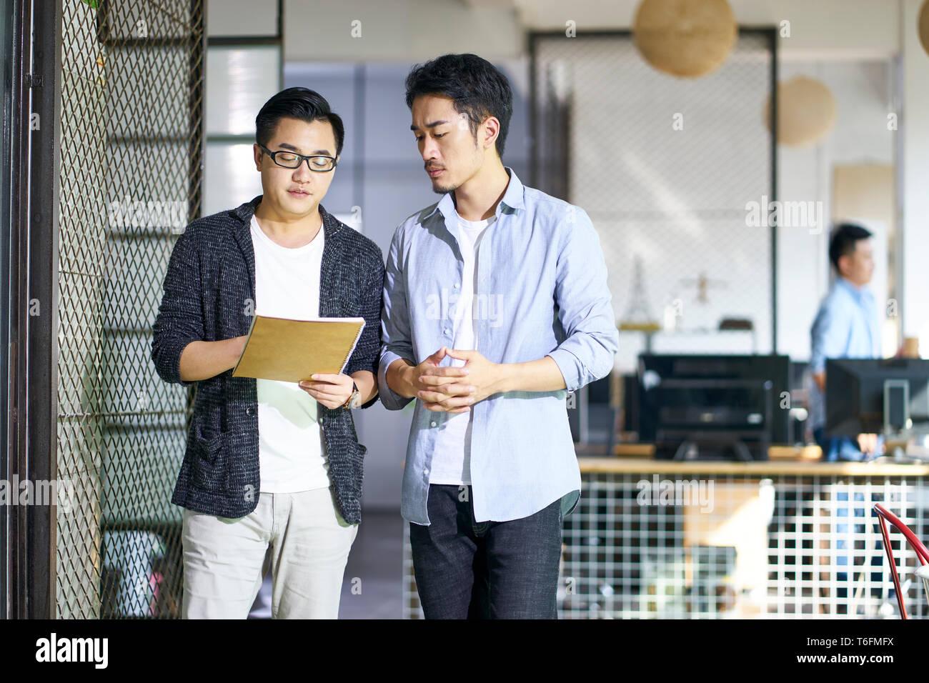 Dos jóvenes compañeros hablando de negocios asiáticos mientras camina en la oficina. Foto de stock