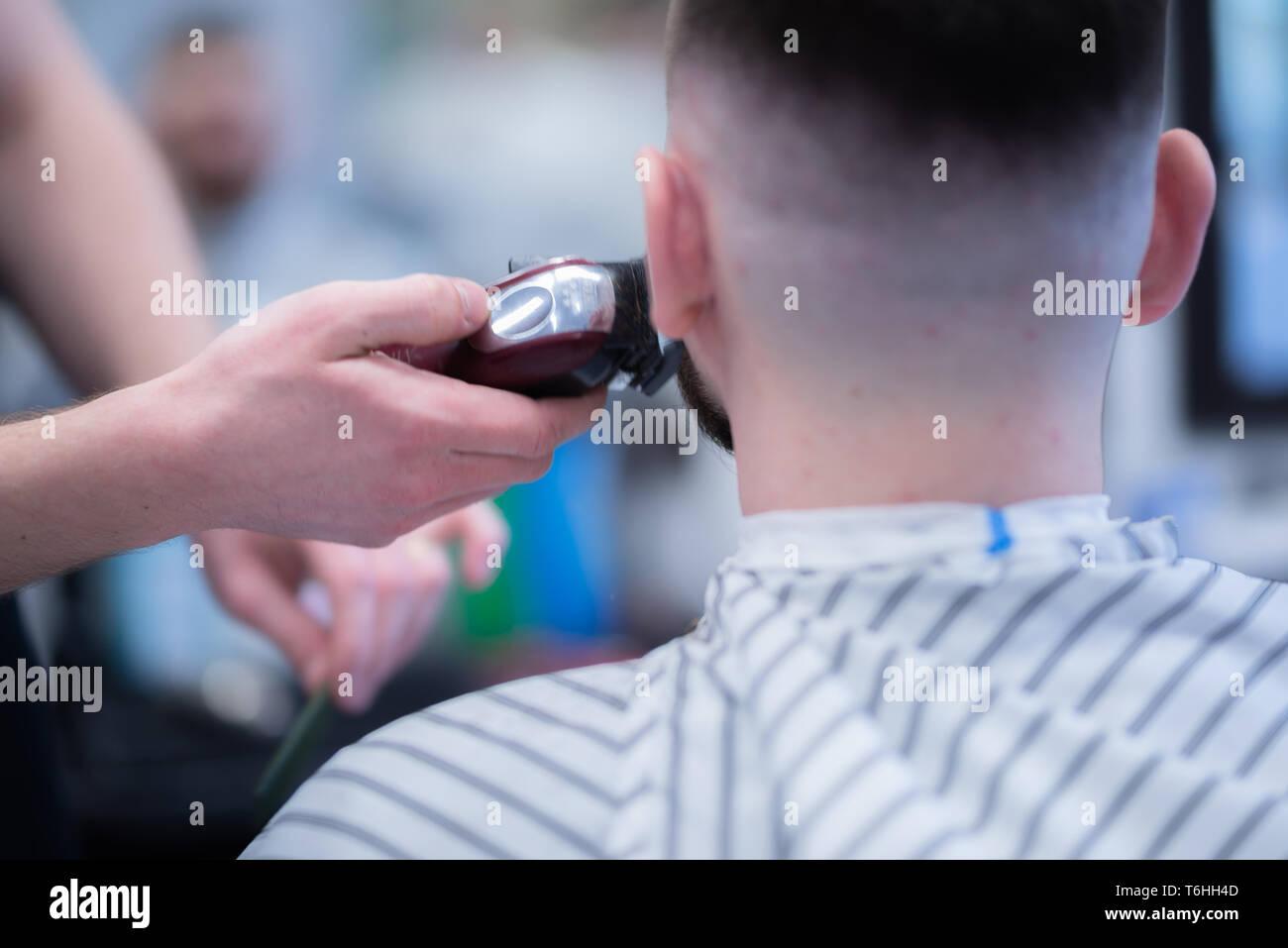 Hombre de corte de pelo en la peluquería. Afeitar una peligrosa de afeitar. Foto de stock