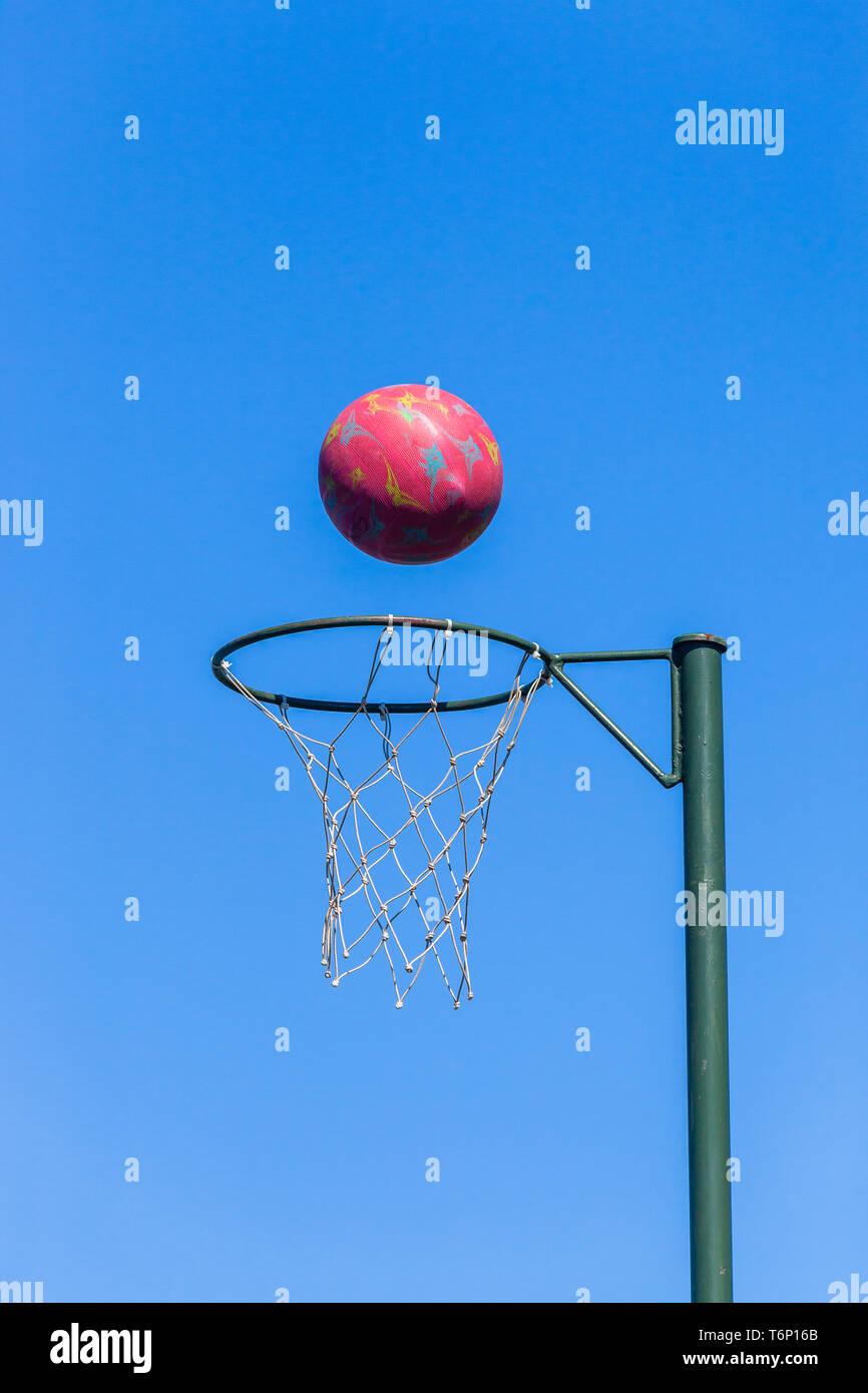 Aro de baloncesto net con bola roja en vuelo contra el cielo azul . Imagen De Stock