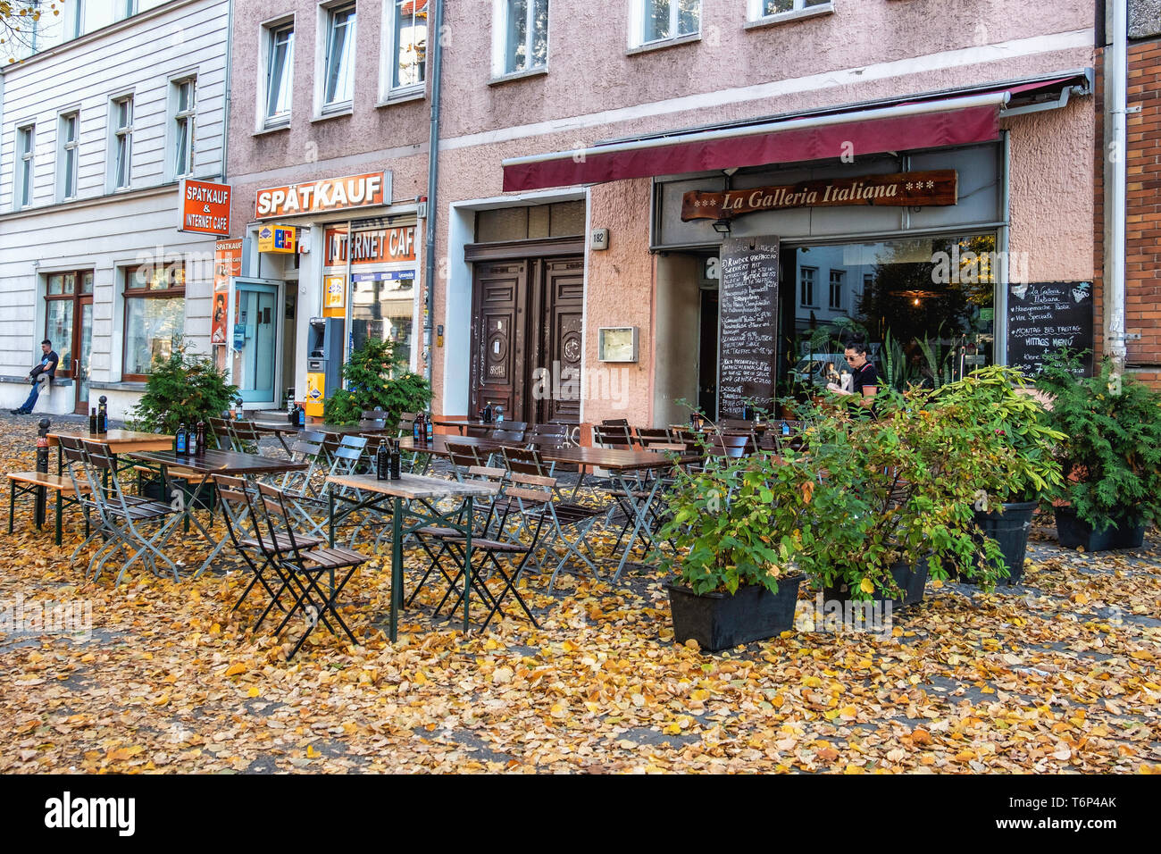 La Galleria Italiana restaurante y tienda de conveniencia en Torstrasse Spatkauf con alfombra de hojas de otoño, Mitte de Berlín. Imagen De Stock