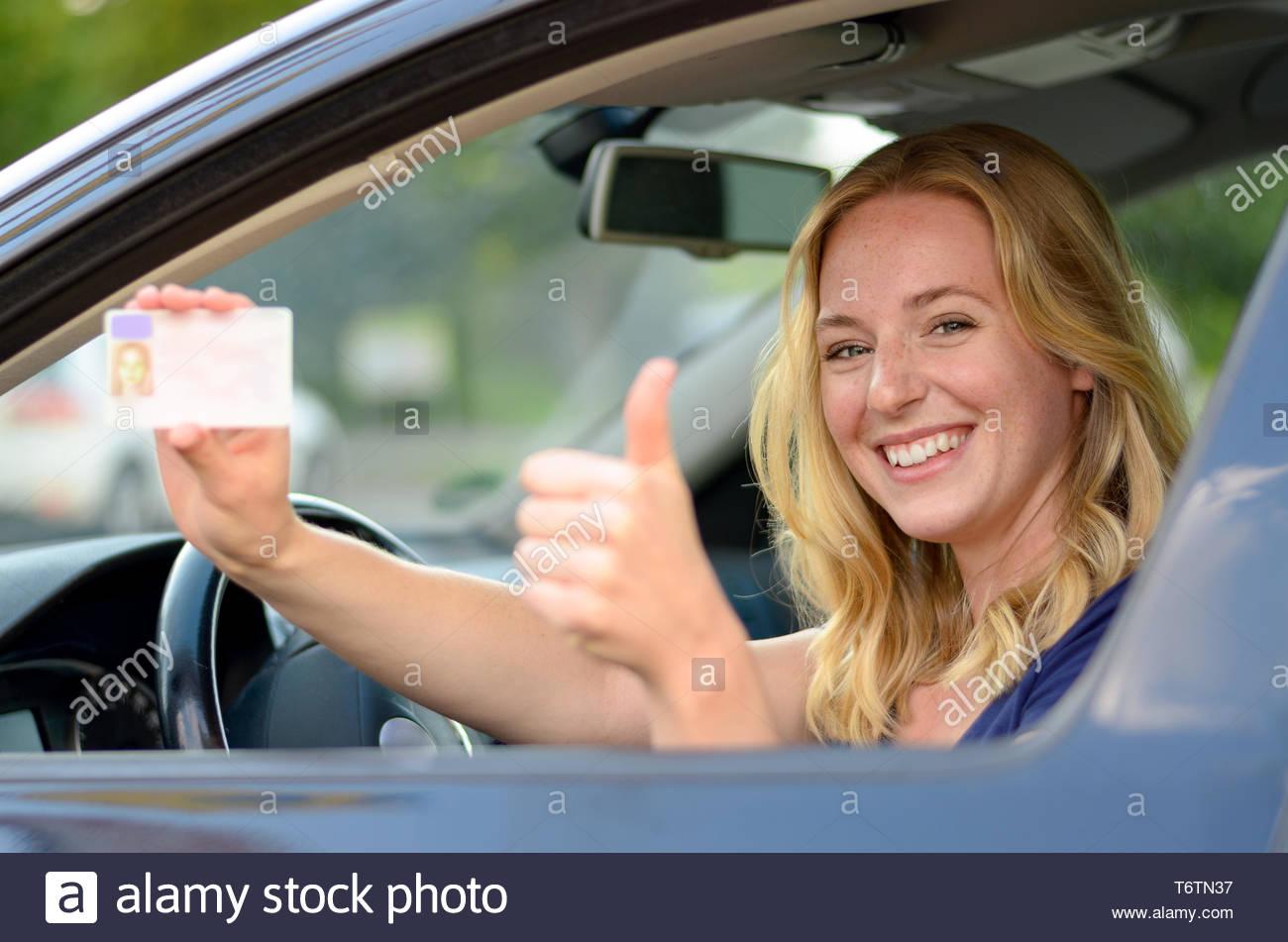 Joven Mujer rubia mostrando su licencia de conductores Imagen De Stock