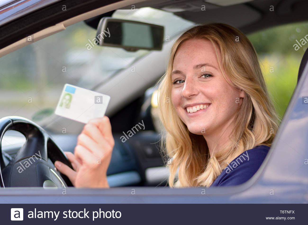 Feliz joven mostrando su licencia de conductores Imagen De Stock